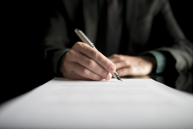 A man in a suit signing a will document